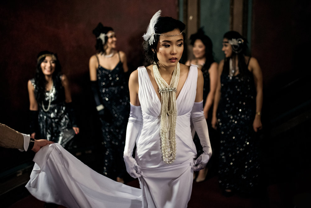 Beatuful bride's white backless gown and 20s inspired feather head piece and pearl necklace with bridesmaids wearing black sequin gown