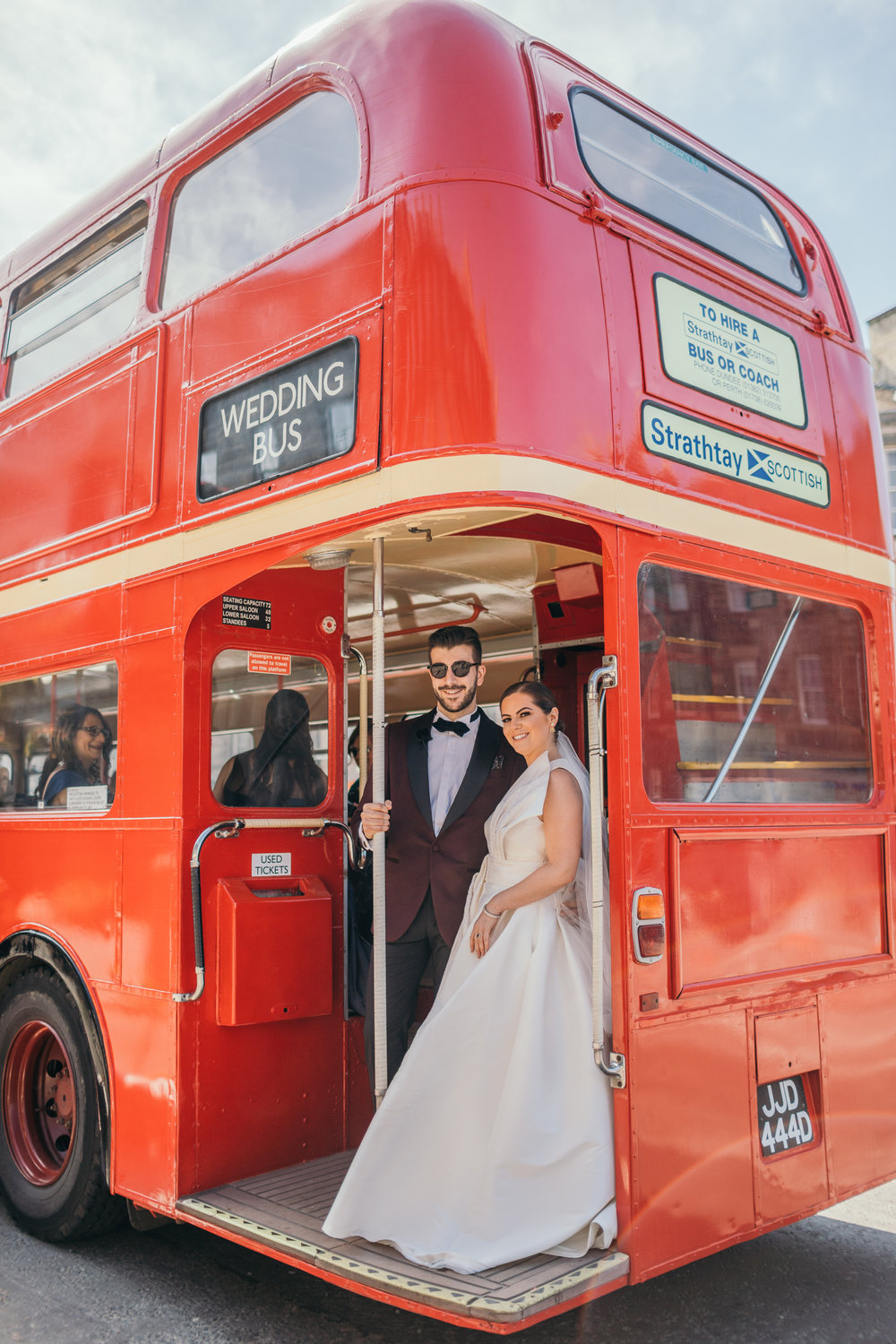 Portrait bride and groom in red double decker bus in Scotland Castle Outdoor Destination Wedding