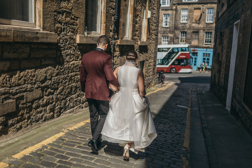 First look of bride and groom walking on cobble stone street in Scotland Castle Outdoor Destination Wedding