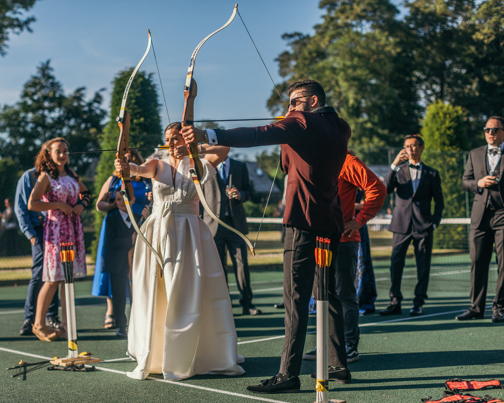 Bride and groom shooting bow and arrows in Scotland summer castle outdoor wedding