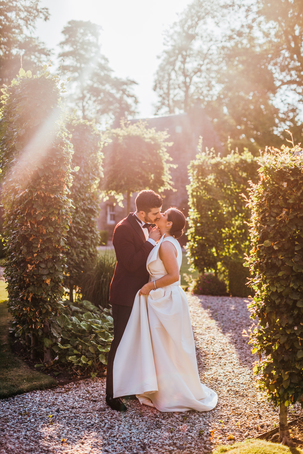 Beautiful portrait of bride and groom kissing outside the Scotland castle surrounded by greenery