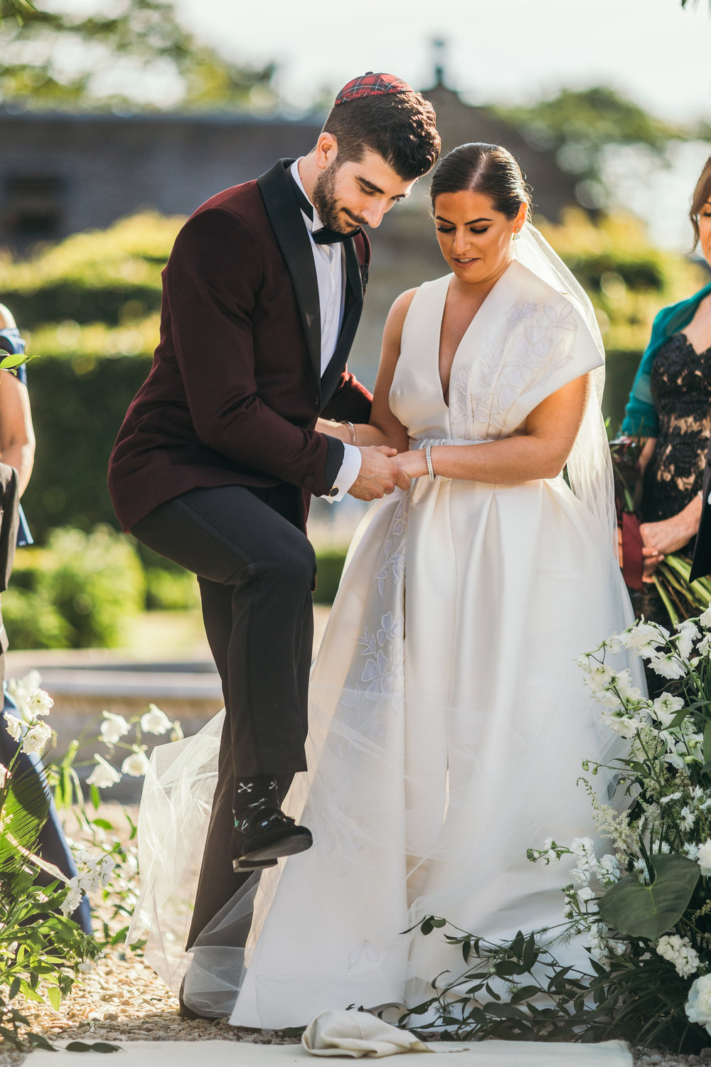 Bride and groom stepping on glass during jewish ceremony in Scotland castle outdoor wedding