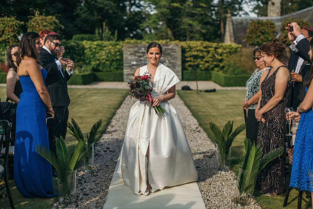 Beautiful bride walking down aisle with organic wine flower bouquet wearing ivory one shoulder wedding dress in outdoor castle ceremony