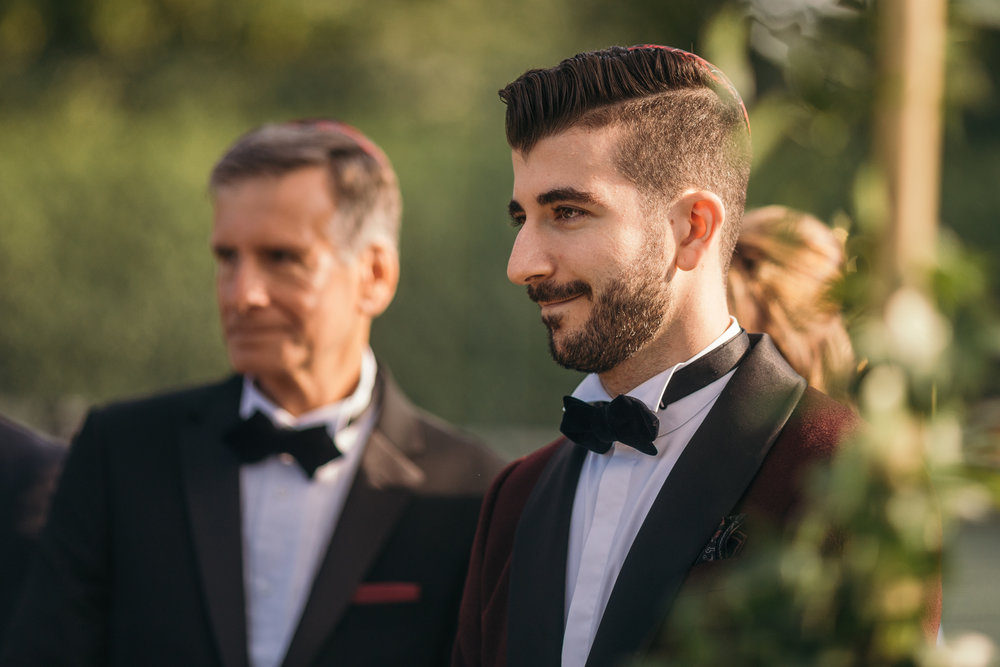Portrait of groom waiting for bride during Scotland outdoor summer wedding ceremony