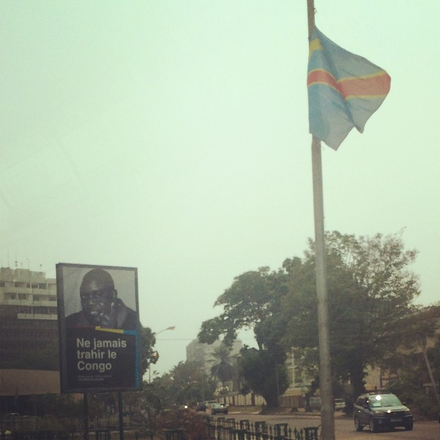 "A billboard, that translates to ""Never Betray Congo"" in English."