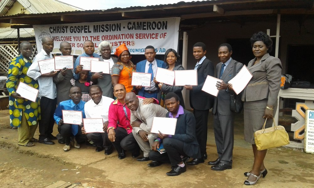 This is a photo of over a dozen people posing for a photo. Most of the people are holding certificates. The pastor in the front row center wearing a red shirt and kneeling. Behind everyone is a poster that says Christ Gospel Mission Cameroon.