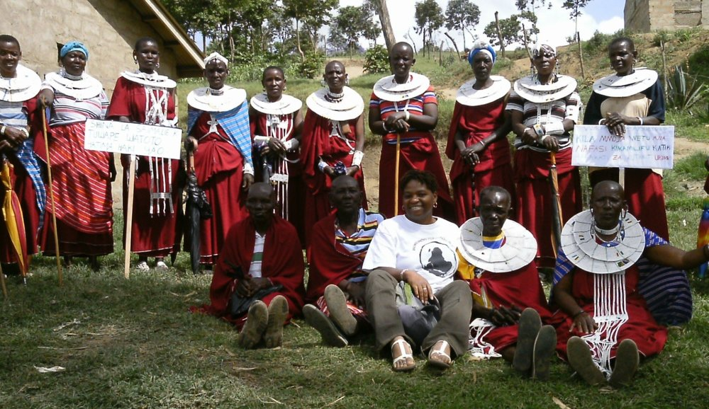 Michelle surrounded by Massai women in Arusha, Tanzania. The women spoke with her about how HIV has affected their community. She also offered the group homeopathic services.