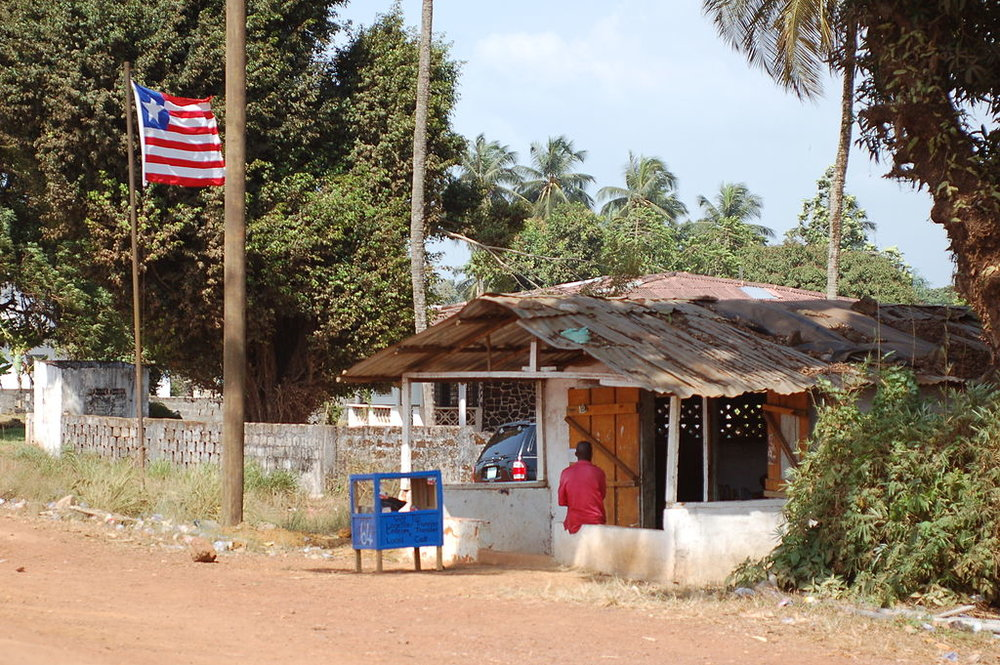 A Liberian flag blowing in rural Liberia. Credit:  Erik (HASH) Hersman  from Orlando,  Liberian flag and duka ,  CC BY 2.0