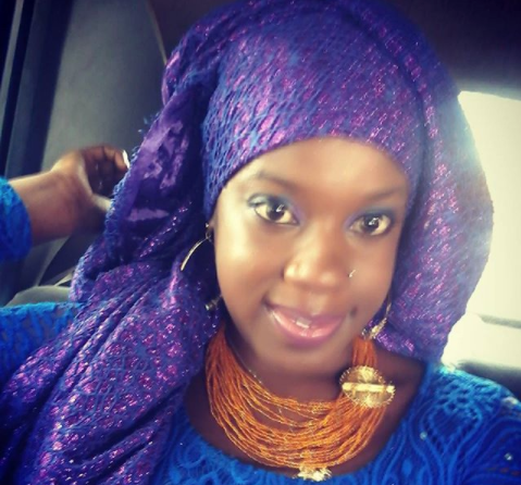 This is a photo of an African American woman (Waameeka, the interviewee) wearing traditional garb: a purple head wrap, orange beaded necklace and blue dress.