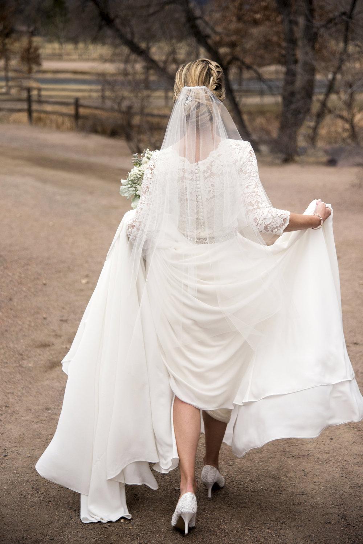 Bride walking, lifting her dress's train | Brad and Mike's Outdoor Wedding at Hudson Gardens | Colorado Springs, Colorado | Farm Wedding Photographer | Apollo Fields Wedding Photographer