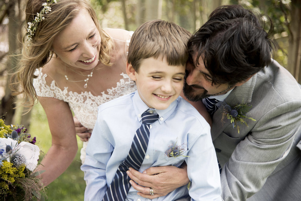 Zach and Susan | Bride and Groom Embracing Child | Intimate Wedding at Gold Hill Inn Boulder Colorado | Farm Wedding Photographer | Apollo Fields Wedding Photojournalism