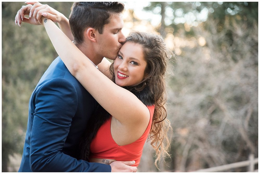 Man Kissing Woman While She Looks at Camera | Nicholas and Eden's Surprise Proposal at Glen Eyrie Castle | Colorado Springs | Farm Wedding Photographer | Apollo Fields Wedding Photojournalism