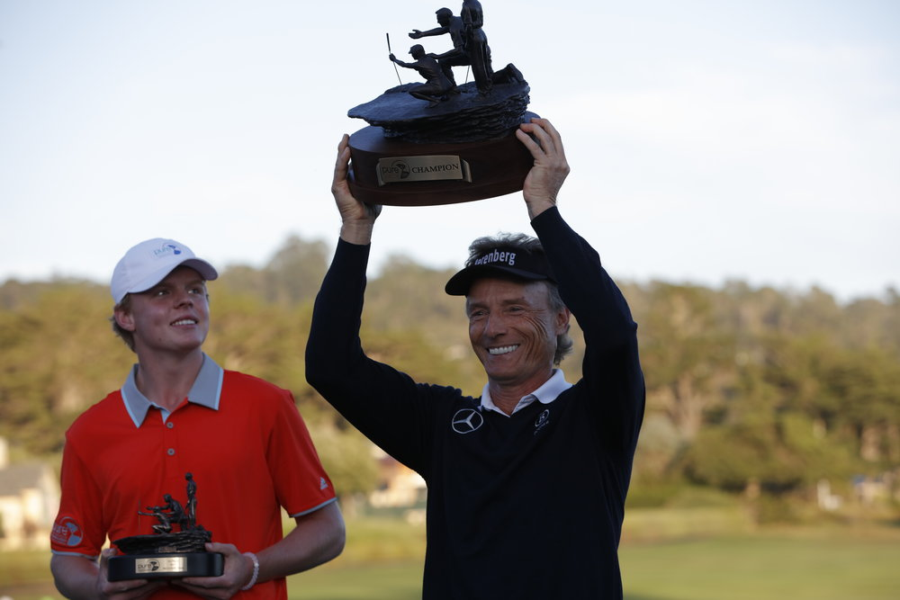 Justin Potwora (left) from The First Tee of Greater Portland and Bernhard Langer (right) display their winning trophies.