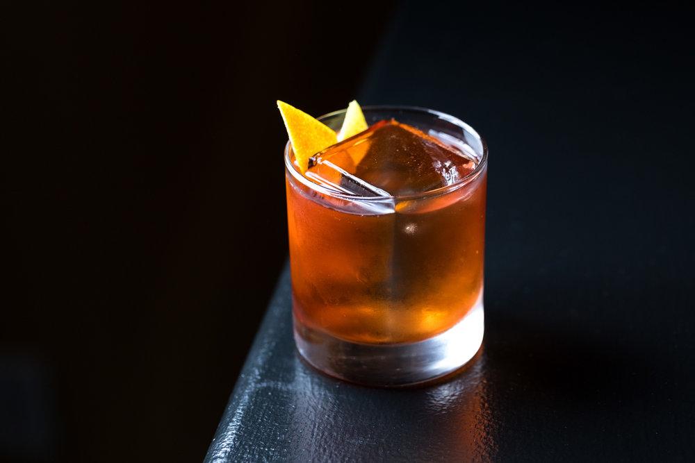 Whiskey drink in tumbler on corner of black bar with lemon garnish.