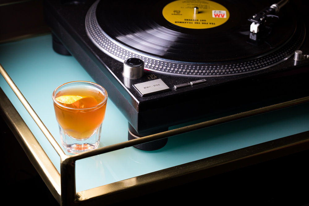 record player with shot of whisky next to it