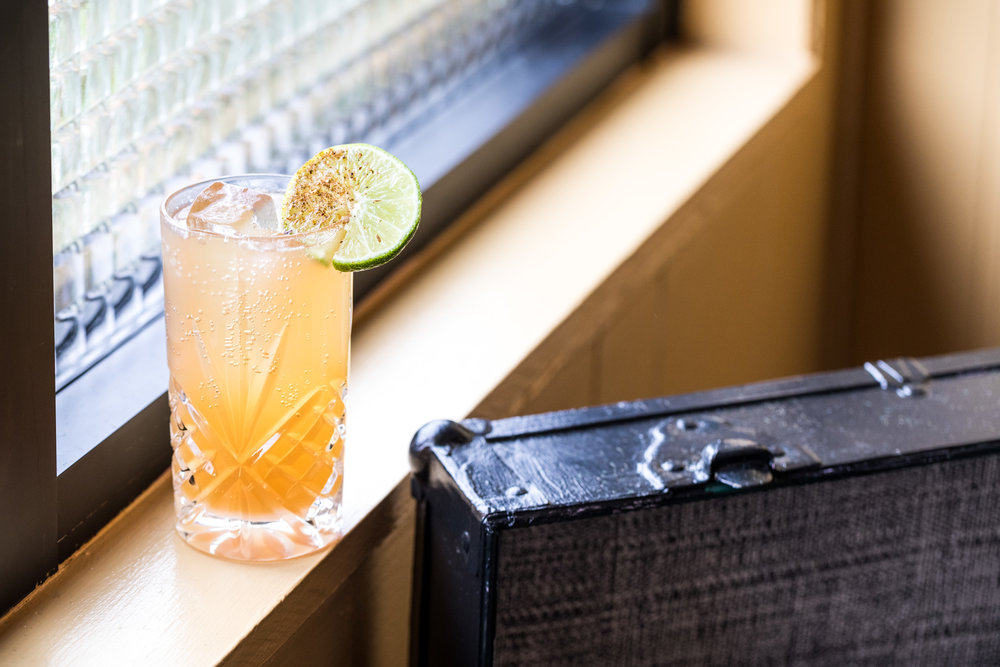 Yellow cocktail with lime garnish sitting on window sill
