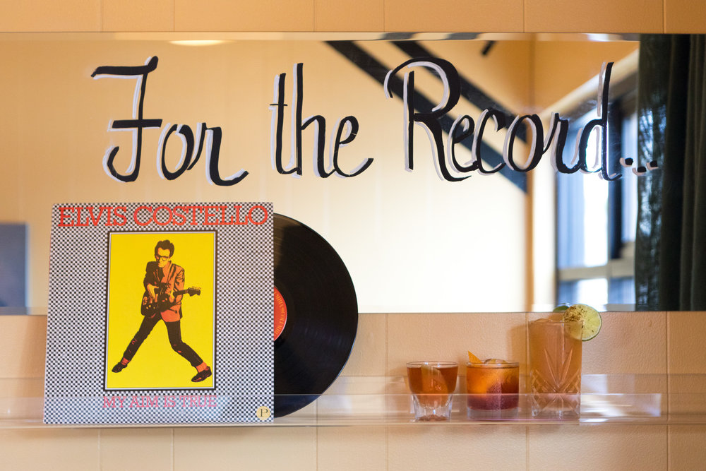 "Mirror with words ""For the Record"" painted in black cursive. Below that, clear plastic shelf with Elvis Costello record and 3 cocktails."