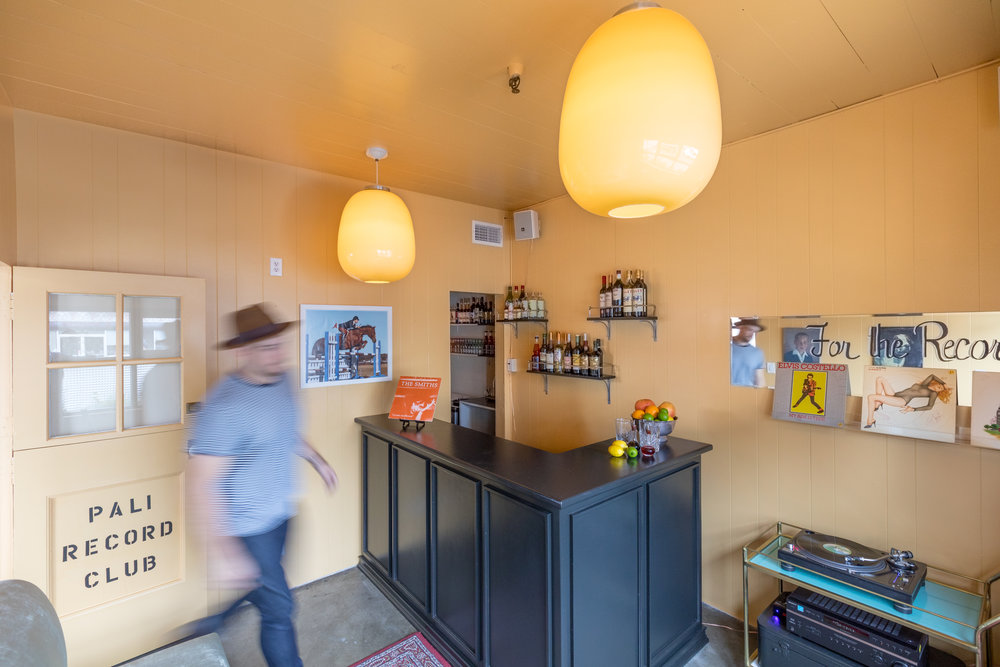 Shot from upper left corner of room. Yellow walls, oversized ceiling lamps, black corner bar with alcohol on shelves in the back. Bartender walking to record player.