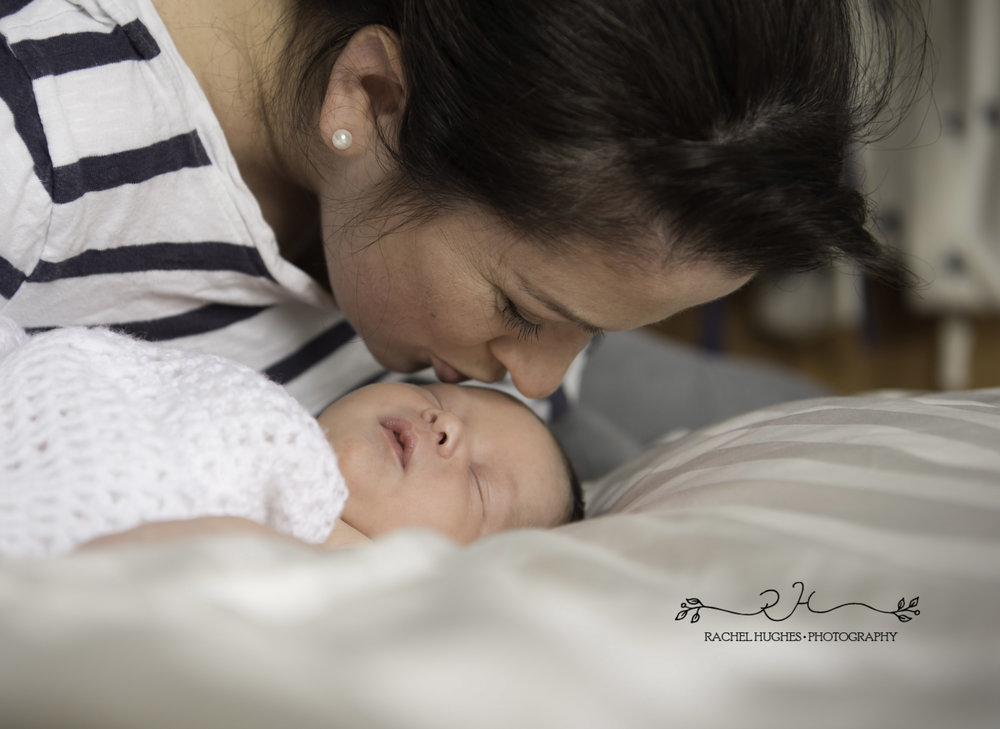 Mother kissing newborn at home