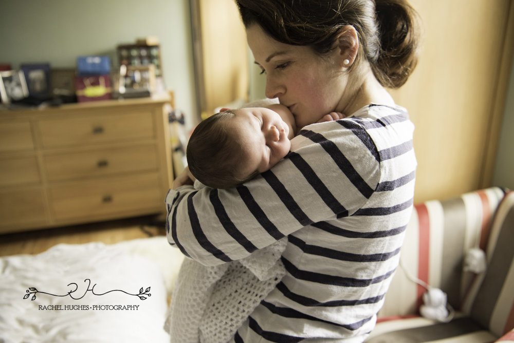 Mother kissing newborn in bedroom