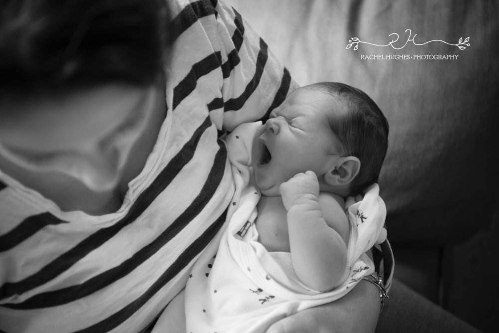 Newborn yawning in mother's arms