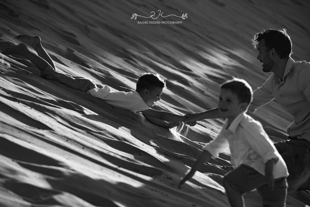 Jersey photographer - father and sons playing in sand dunes