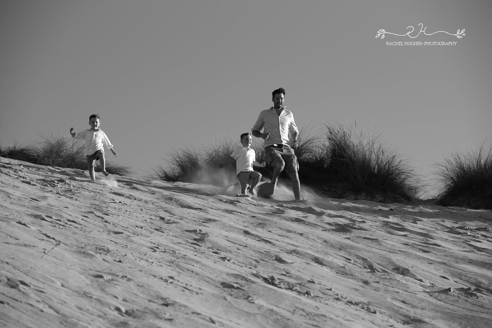 Jersey photographer - father and sons running down St Ouen's dunes