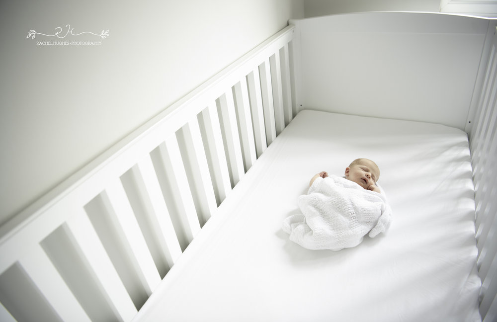 Jersey photographer - tiny newborn in cot
