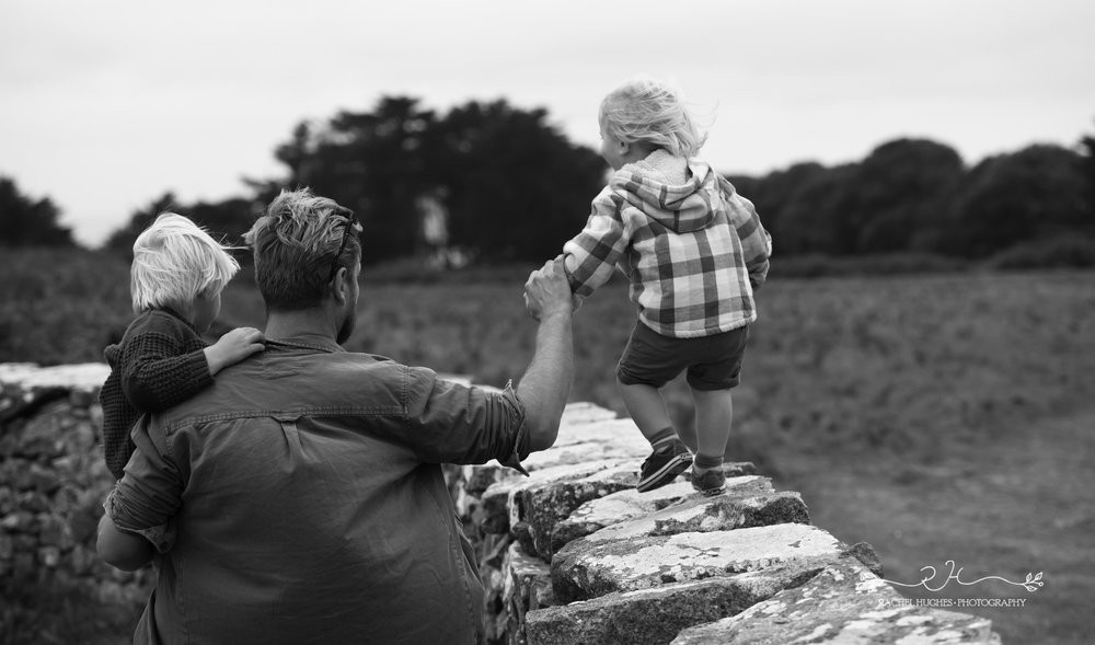 Jersey photographer - dad holding boy on wall
