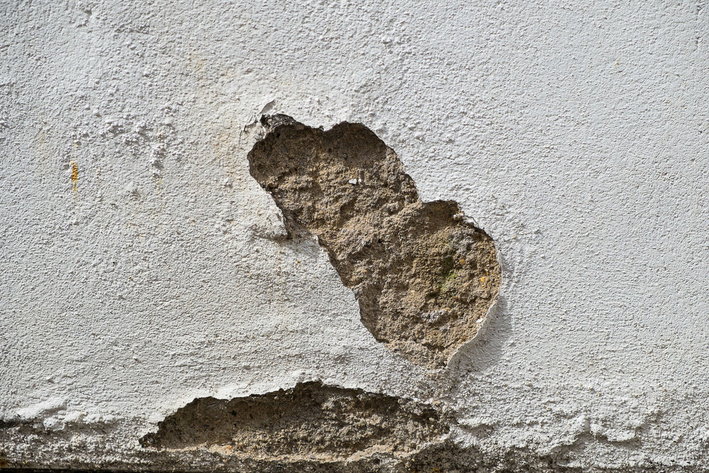 outside wall showing patch of damaged render