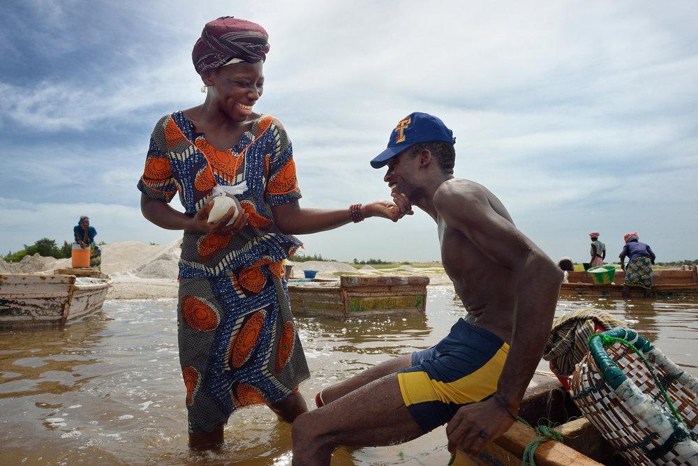 18. September 2012.Eine der Arbeiterinnen reicht einem Salzgräber lachend eine Plastiktüte mit Trinkwasser. Die Frauen und Männer am Lac Rose arbeiten fast täglich zusammen und sind wie eine grosse Familie.