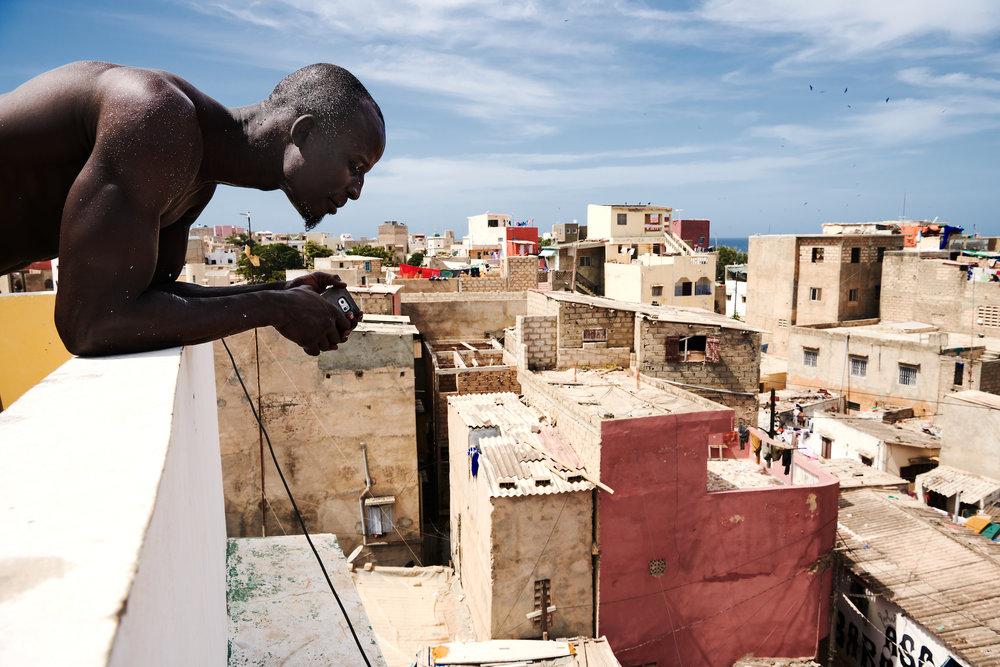 """4. November 2017. Kehrou Ngor blickt vom Dach des Hauses seines Onkels auf die Straßen des Quartiers Ngor in Dakar. Als angesehener Ringer spielt er auch die Rolle eines Wächters.. """"Es gibt keine Diebe in diesem Quartier."""" sagt er grimmig. """"Jeder weiß, was ihn erwartet, wenn er hier stiehlt."""
