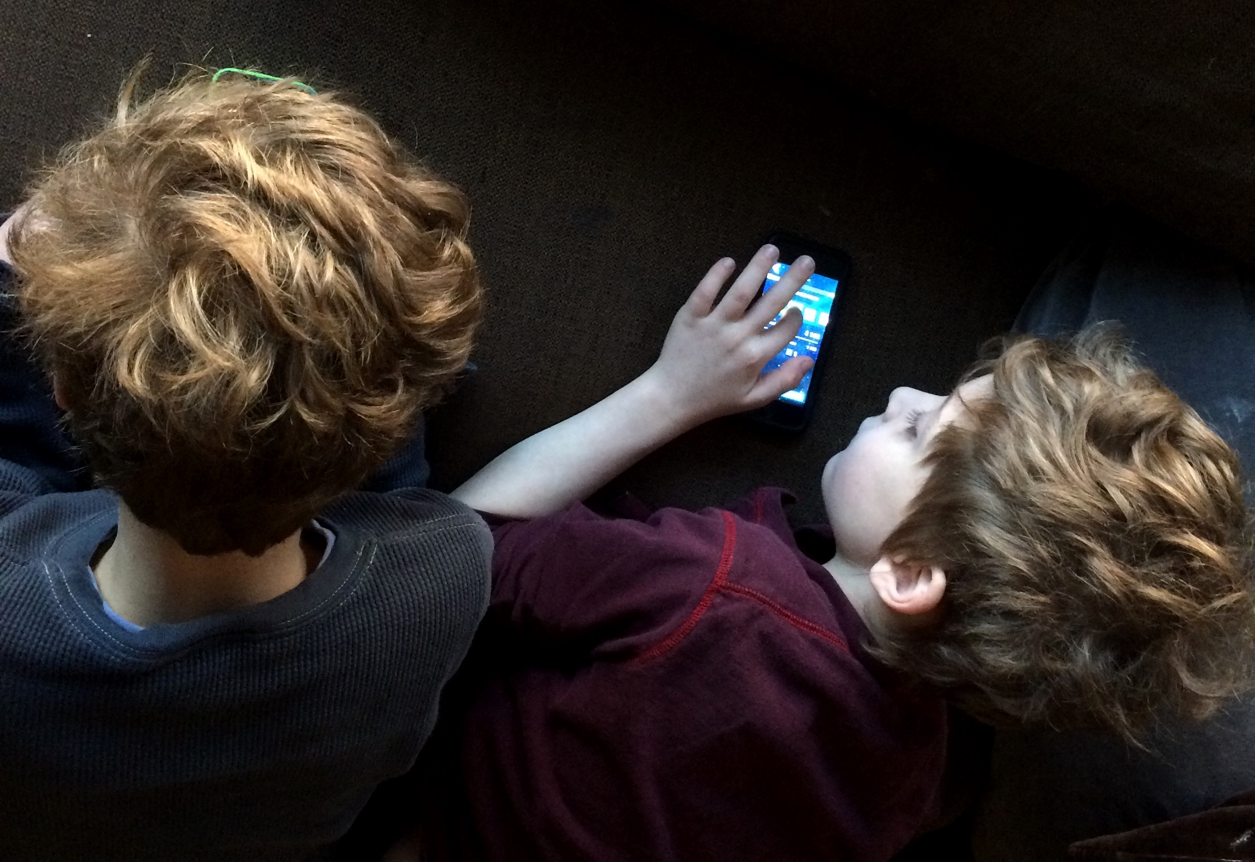 M and C, twin brothers, playing electronic devices next to each other