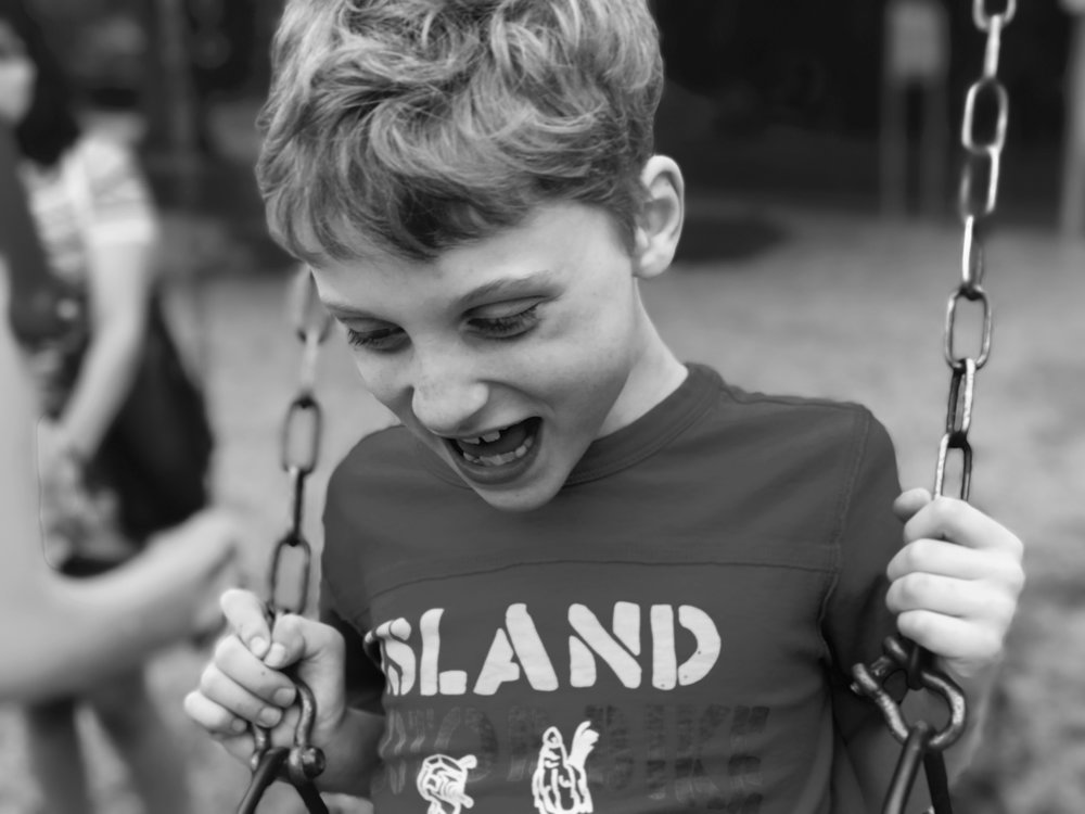A young autistic boy laughs with joy while sitting on a swing in a playground.
