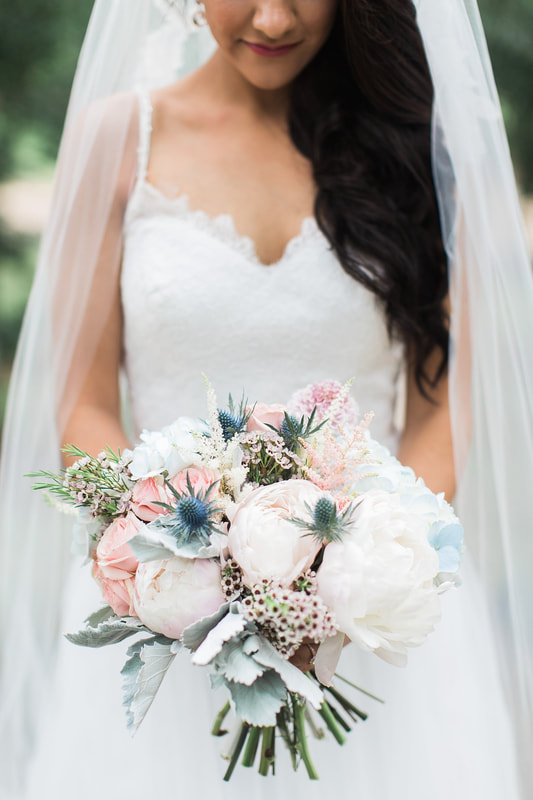 The bride's bouquet was an original design, full of peonies, wax flowers, dusty miller, scabiosa, and thistle. The mix of the pinks and blues highlighted her beautiful bridesmaids' dresses and complimented the cobalt blue of the men's attire.