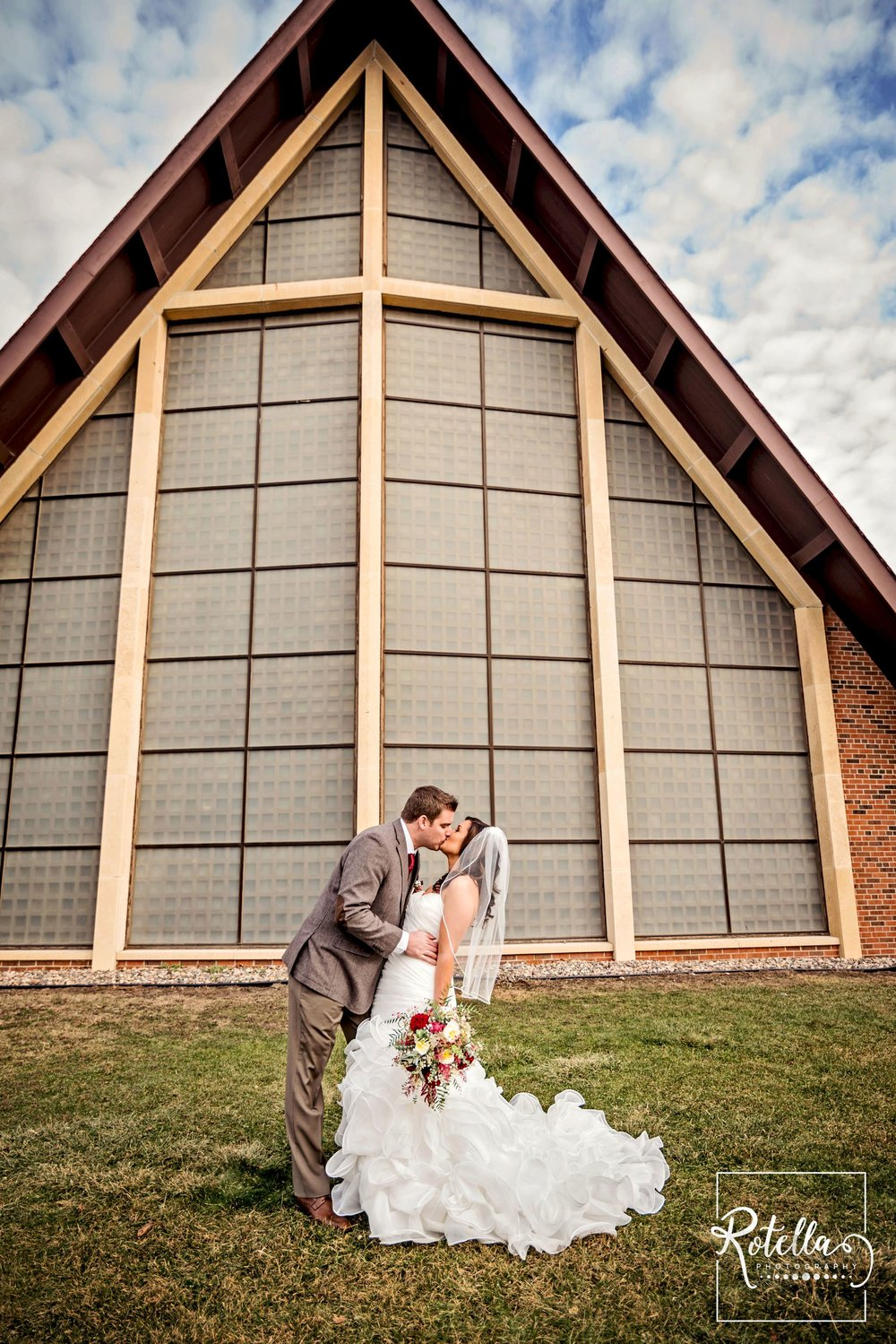 bride and groom kissing in front of church with green grass
