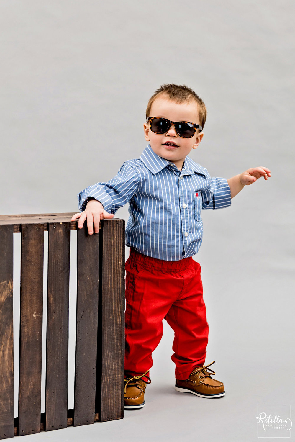 Rotella Photography baby smiling with sunglasses on grey backdrop