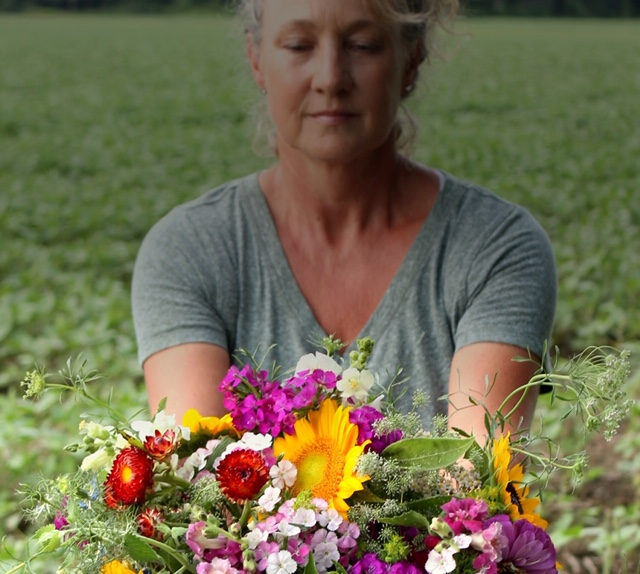 Farmer Kathy sharing the Farm's bounty of flowers with you