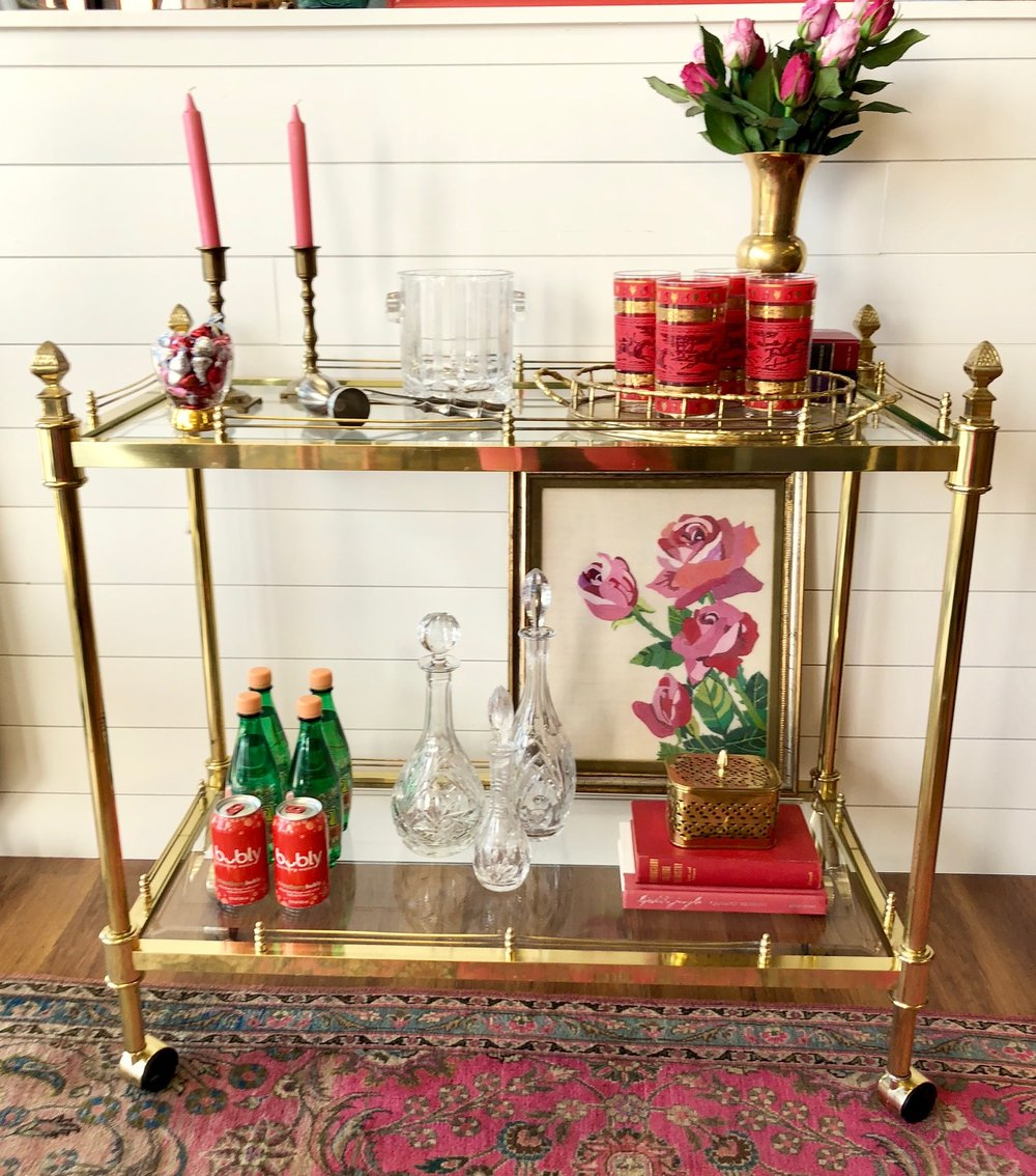 The bright pink and red accessories pop against the sheen of the mint condition brass bar cart.