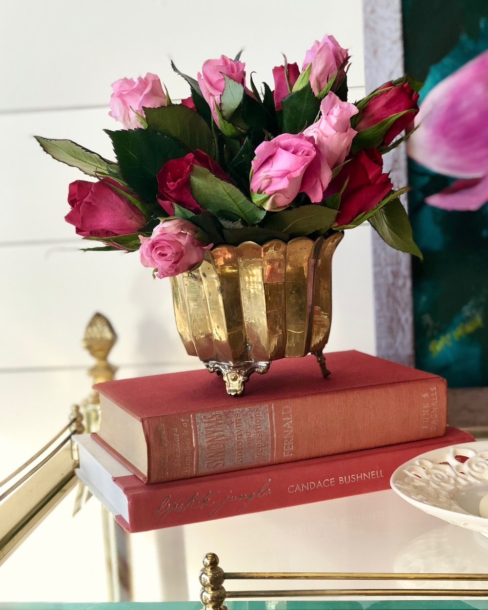 Having a gilded vase or small urn for flowers makes it convenient to display—as are books to create a pedestal for showing them off.