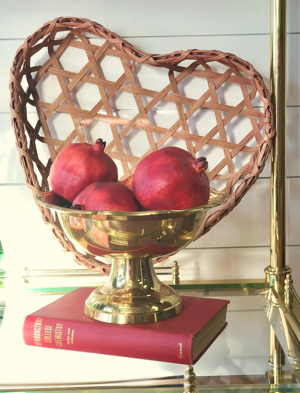 Lush pomegranates in a brass bowl echo the color scheme without being too cheesy, but the heart shaped basket in the background subtly prompts to the special holiday.