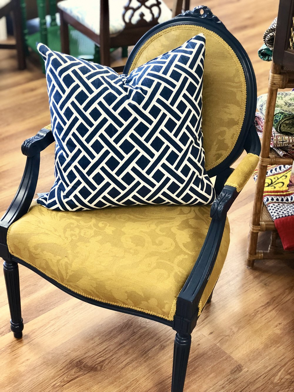 The damask fabric and the shape of the chair say traditional, but the golden hue of the covering and the geometric pillow make an updated statement.