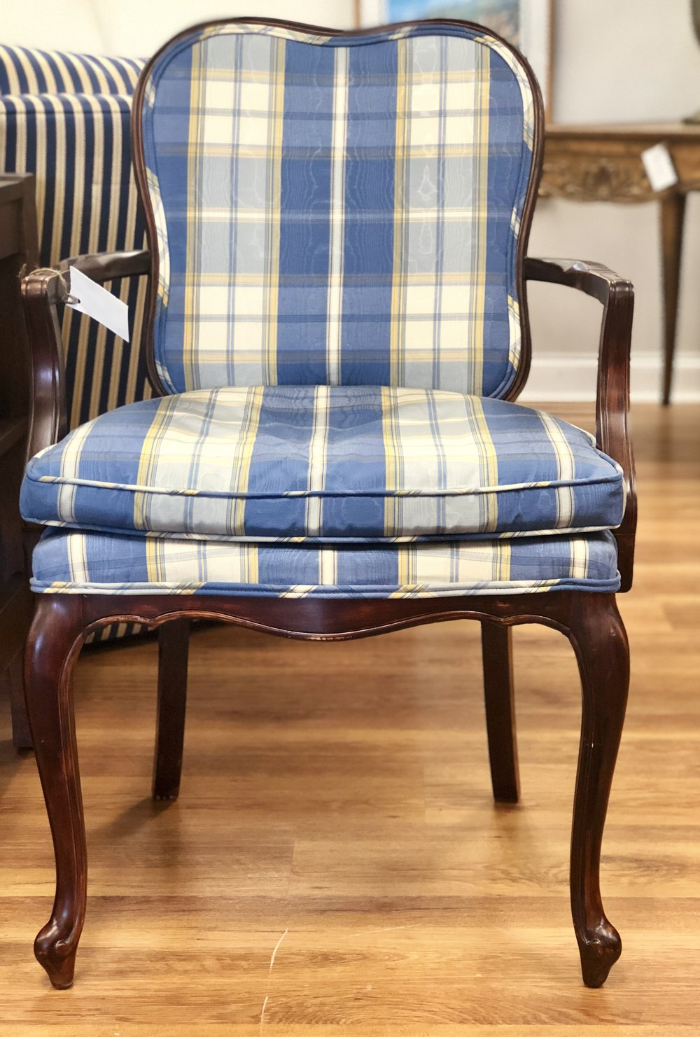 The juxtaposition of the feminine curve on the back of this chair with the masculinity of the plaid fabric bring an overall balance to this classic piece.