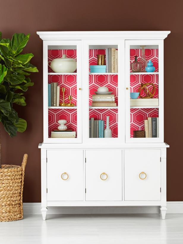 Photo Source:  HGTV   The pink geometric pattern is truly the star in this cabinet showcasing clean and simple home accessories.