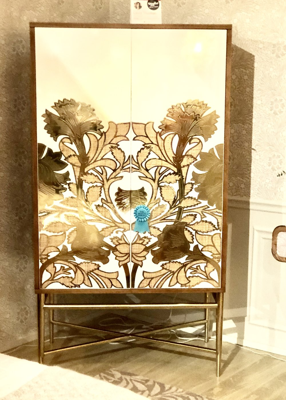 Notice how this large piece incorporates many trends: the bright brass, wicker underneath the pattern, and glossy white as a background for the floral motif.