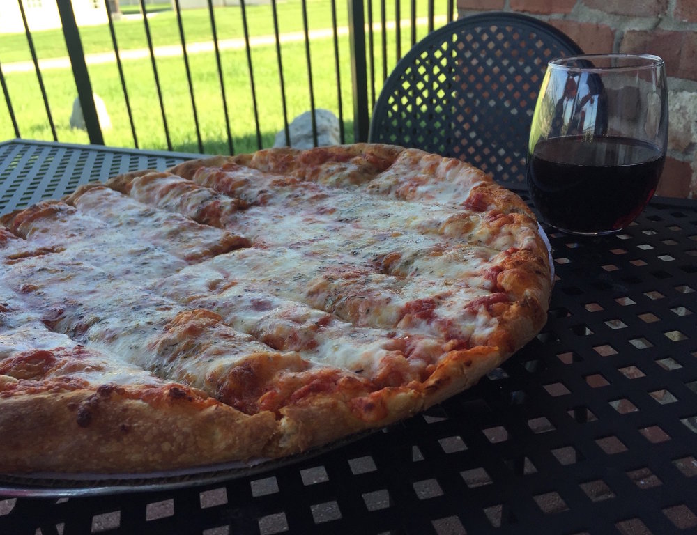 signature Quad Cities style pizza - This traditional recipe started almost 50 years ago as an original Midwestern take on incredible pizza. Our crust is homemade, hand-tossed, and perfectly baked with a unique blend of dark roasted brewer's malt, creating the perfect soft yet crisp and airy texture we all crave.