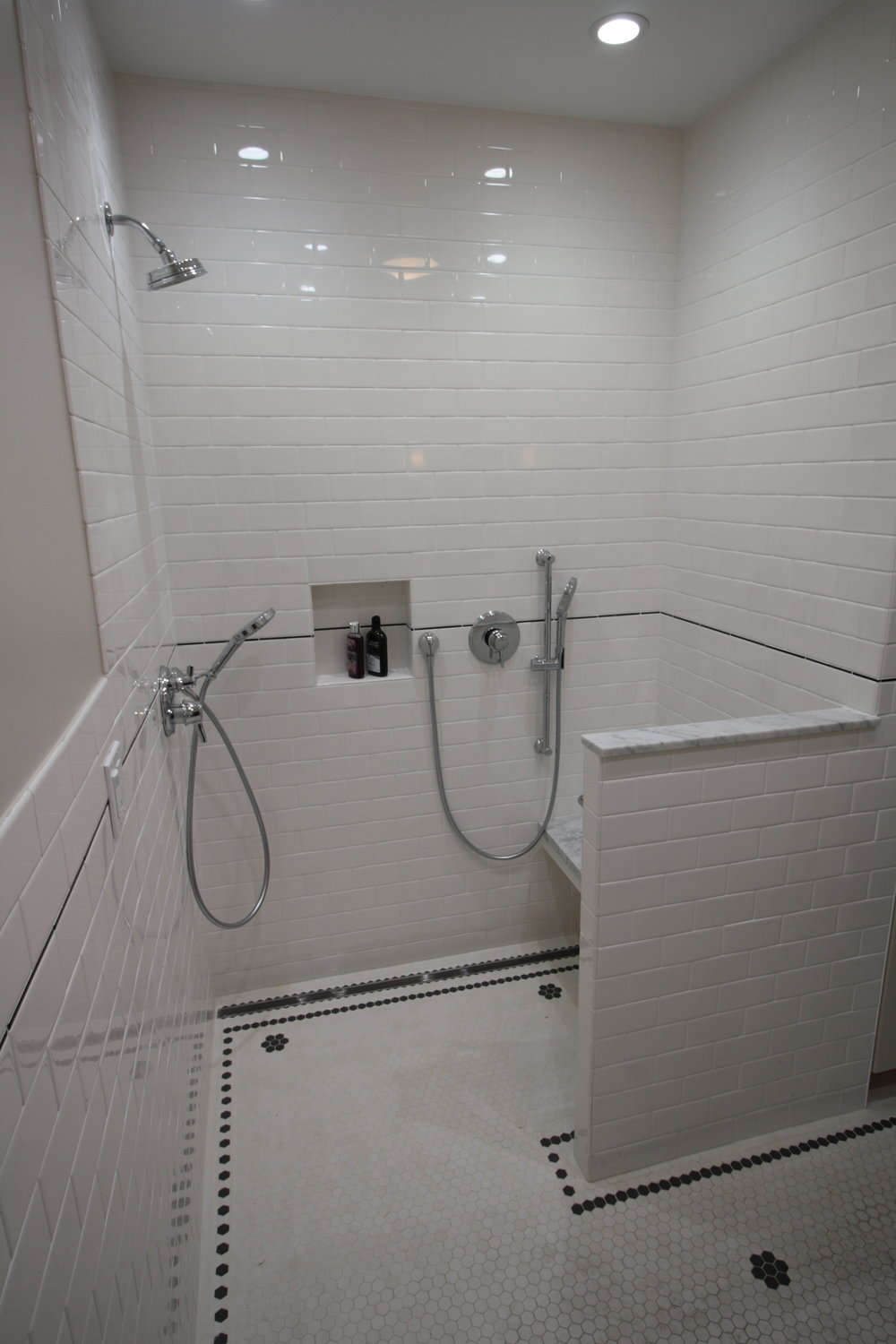 A shower that works standing or seated (prior to glass installation). Individual controls allow for direct use no matter where the bather prefers to shower.