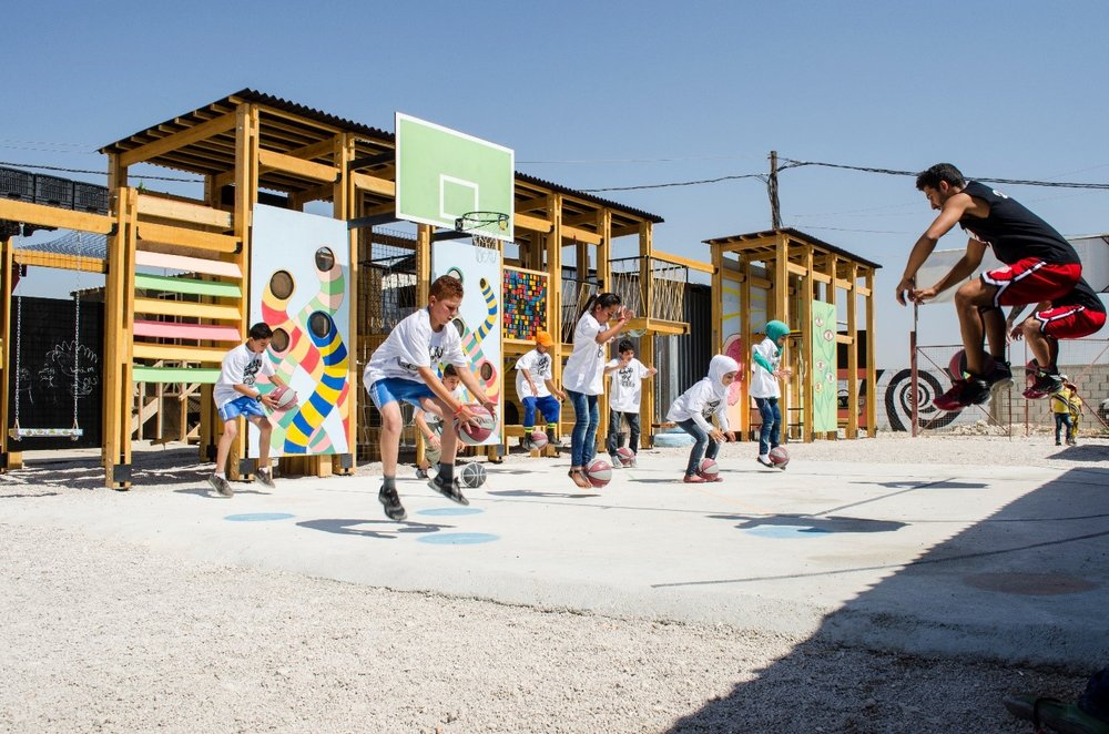 """IBTASEM playground in Lebanon          Source: Catalytic Action http://www.catalyticaction.org/all-project-list/playground-syrian-refugees/ - This time last year, I was reading a book called """"Design like you give a damn: architectural responses to humanitarian crises[1]."""" by Architecture for Humanity (AFH). It was interesting to find out that although the phrase """"humanitarian architect"""" was repeatedly used in the book, the title framed it as """"architectural responses to humanitarian crises"""", perhaps in response to the debate that all architects wish to do good and that separating humanitarian architects from the others may form further barriers.To me, the difference between what is humanitarian or not lies in the context of practice rather than the goal of practitioners. Architectural practice in the humanitarian field has only begun to be noticed in the last two decades, especially after the 2004 Indian Ocean Tsunami. In the context of intensified natural disasters, forced displacement and consistent global poverty, the crisis has been protracted and the boundary between temporary and permanent, between humanitarian and development, have been blurred. In the old days when people were only going to be displaced temporarily, a simple shelter (often in the form of a tent or an isobox) would suffice; it was engineers rather than architects who provided solutions. The most important evaluation criteria were efficiency and financial feasibility.Nowadays when the average time of displacement of refugees are 17 years (according to UNHCR), temporary solutions are not enough.The physical environment impacts people's mindsets. Sharing a room with 7 strangers deprives any right to privacy; living in endlessly repeating isoboxes deprives people of identity. Surviving in """"minimalism"""" without amenities deprives the sense of community. In a word, people suffering from humanitarian crises are exactly those who aspire for normalcy, for all the simple things they could do before every"""