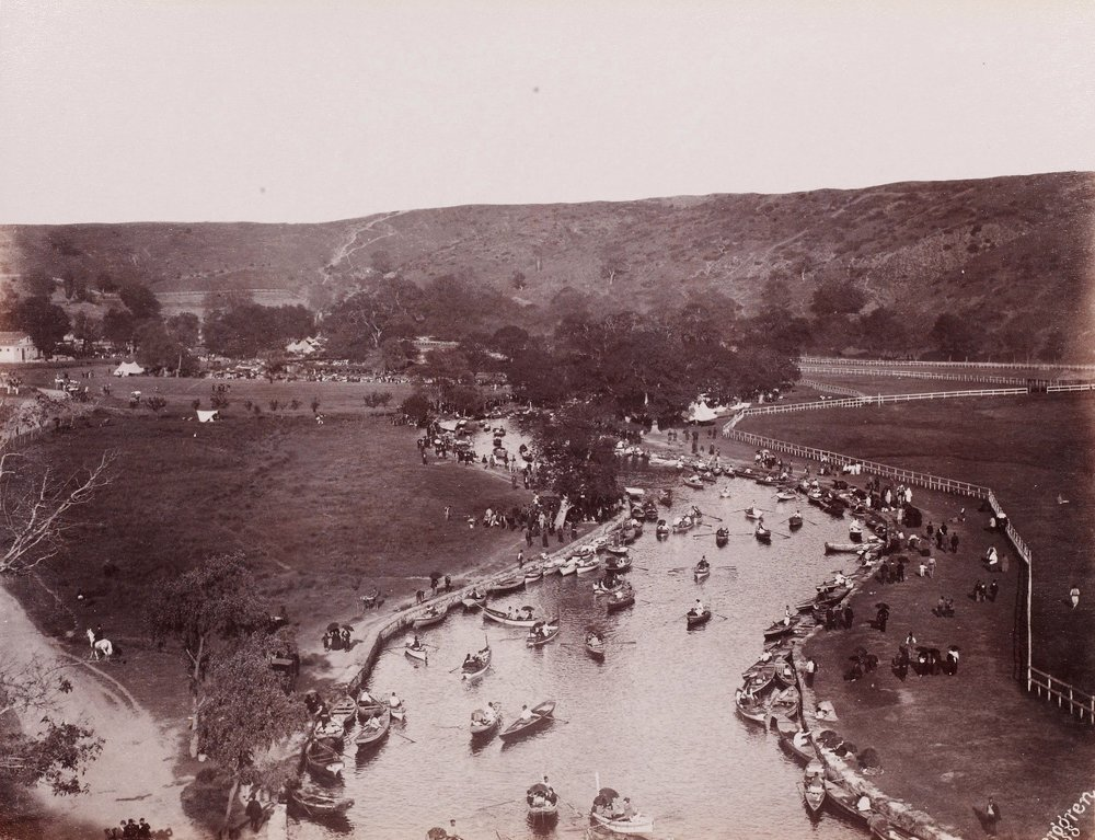 """Image Credit / Bibliography:Kağıthane River - Sadabad (1880s) by Guillaume Berggren - Proliferation of public parks is one of the key defining features of the changing urban fabric of 19th century Istanbul. Most scholarship has interpreted this proliferation merely as a symptom of the Western influenced modernization of the city. However, these public parks are also important to examine from a social lens because they are emblematic of shifts happening between the public and private spheres of an increasingly cosmopolitan Istanbul.The notion of public space in Istanbul is of course not confined to this current era of modernization. Courtyards of mosque complexes (kulliyes) functioned as gathering places for decades before the emergence of public parks. At this time, this notion of public space was confined to the mosque's site where there was still a clear separation between the private (domestic) and public sphere. This separation started becoming less apparent in the 18th century with the opening of imperial gardens to the general public. Sadabad, the imperial garden constructed in 1721 by Ahmed III and reminiscent of Versailles with its winding paths around artificial pools and marble-paved river banks, allowed the public to pass freely from the public promenade of Kağıthane to the imperial palace grounds to entertain themselves in this space. This typology began blurring social spaces between the ruling elite and the public, making Kağıthane one of the most popular excursion spots in Istanbul. Countess de la Ferté-Meun visiting Istanbul in 1816 describes the Kağıthane scene as such: """"[…] the sound of this cascade at your feet, these groups of Turkish, Greek, Armenian and Jewish women whose mores, customs and outfits are so varied and who delight, undaunted, in all sorts of divertissements the countryside [has to] offer, make this promenade a ravishing spectacle.""""The spectacle of the diversity of visitors in these new parks evolved into a 'see and be seen' dynami"""