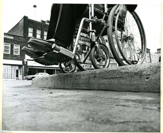Inaccessible kerb, late 20th century. Division of Medicine and Science collections, Smithsonian. - The built environment has historically been designed for idealised and standardised bodies, an approach which dates back at least to Vitruvius' proportioning systems, and which was popularised and further developed in Europe throughout the Renaissance and centuries beyond. In more recent history, this approach to design is enforced and perpetuated by building codes and industry standards as well as documents like Ernst Neufert's Architects Data and systems like Le Corbusier's Modulor.[1] The major problem with these codes and systems is that by designing for a standard, or norm, they encourage a design response which generalises the human condition. It is surprising that, in the 21st Century, when we are more aware than ever of the breadth of human needs and expression, our contemporary designs for the built environment are still intrinsically marginalising in ways that are both subtle and overt, for people whose needs deviate from this idealised norm.In 2011 I presented research [2] into the issues of marginalisation for wheelchair users in relation to available clothing options. Clothing is intimately linked to identity and self-expression. Key observations were that the design of clothing for this group tends to be primarily medical or functional, focussing on safe clothing that is easy to put on or take off like tracksuits or gowns, but overlooks emotional and aesthetic needs of users for self-expression. By contrast, the general clothing market is endlessly diverse, creating huge variety in options for people who are closer to a 'norm' but marginalising those whose needs are different. Furthermore, clothing options which target the wheelchair user community are generally overly pragmatic and often simply ugly. Respondents consistently identified that this sends a clear negative message to them about how they are perceived and valued by society.These issues are not